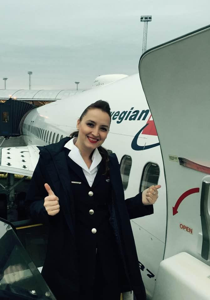 Ce înseamnă să fii însoțitoare de zbor? Livia făcând semnul OK lângă un avion